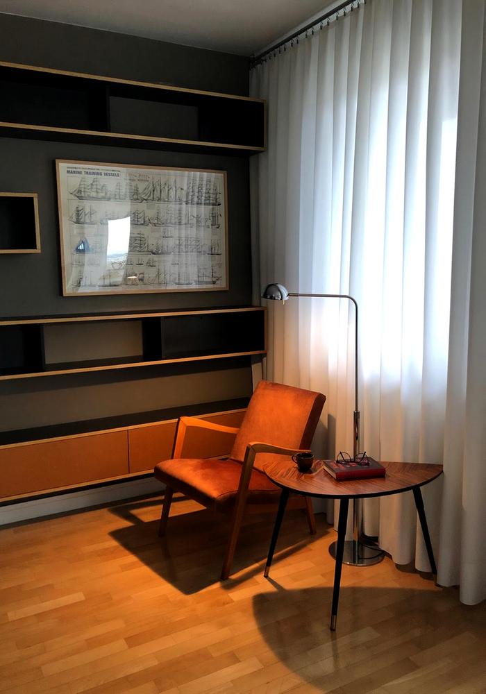 Wnętrze retro - kącik czytelniczy z biblioteką i fotelem PRL